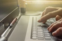 Man is typing on the keyboard of his laptop in the office stock images