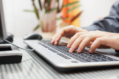 Man  is typing on keyboard at home Royalty Free Stock Image