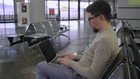 Man is typing on keyboard of laptop in hall in airport stock footage