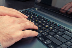 Man typing on a keyboard with letters in Hebrew and English Royalty Free Stock Images