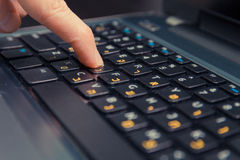 Man typing on a keyboard with letters in Hebrew and English Stock Photos