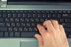 Man typing on a keyboard with letters in Hebrew and English Royalty Free Stock Photo