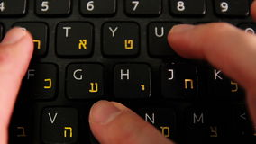 Man typing on a keyboard with letters in Hebrew and English. Laptop keyboard - Top View - Extreme close up - Static stock footage