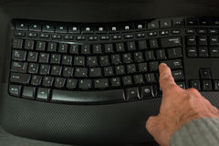Man typing on a keyboard with letters in Hebrew and English Stock Photo
