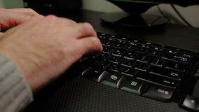 Man typing on a keyboard with letters in Hebrew and English stock footage