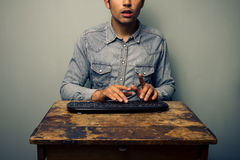 Man typing on keyboard at old desk Stock Photography