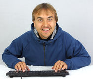 Man typing on keyboard and smiling Stock Photo