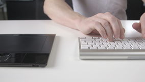 Man typing on the keyboard and use the tablet. Camera panning along the keyboard and tablet when a man typing on the keyboard and use the tablet stock video footage