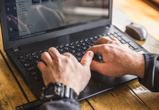 Man Typing on Laptop Computer. Man typing on a small, black or light gray laptop computer Stock Photo