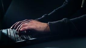 Man typing on laptop keyboard at night stock footage