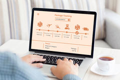 Man typing on laptop keyboard with package delivery tracking scr. Man typing on laptop keyboard with package delivery tracking on screen in room Royalty Free Stock Image