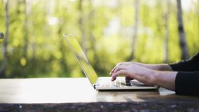 Man typing at laptop keyboard in a park. Close up of young man s hands. He is wearing black clothes and typing at his laptop keyboard. Concept of a freelance job stock footage