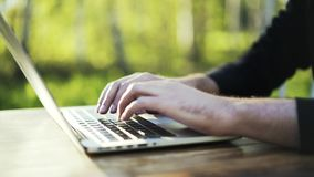 Man typing at laptop keyboard in a park close up. Close up of young man s hands. He is wearing black clothes and typing at his laptop keyboard. Concept of a stock footage