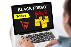 Man typing on laptop keyboard with sale black friday screen Stock Image
