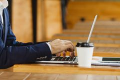 Man typing on laptop sitting with cup of coffee. Man typing on laptop sitting at wooden table with cup of coffee in hand. Male hands on notebook, person in Royalty Free Stock Image