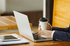 Man typing on laptop sitting and holding cup of coffee. Man typing on laptop sitting at wooden table and holding cup of coffee in hand. Male hands on notebook Stock Photos
