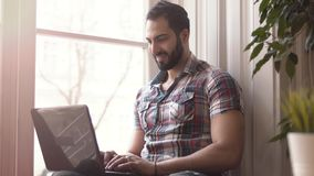 Man typing on laptop. Successful businessman working from home, handsome smiling boy in stylish checked shirt typing on silver laptop cheerfully, sitting stock video