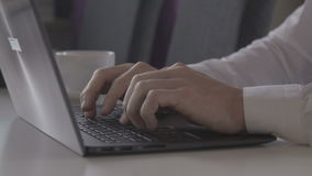 Man typing on a laptop. On a white table stock video footage