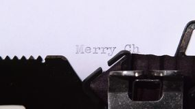 Man is typing a letter on the typewriter of a merry christmas. Close up. Man prints a letter on the typewriter of a merry christmas, congratulates his family and stock video footage