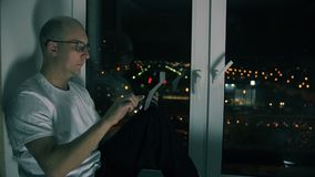 Man typing message in social networks on screen tablet pc sitting on windowsill. Handsome man in glasses typing message in social networks on screen tablet pc stock video