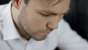A Man is Typing a Message Using his Mobile Phone at Evening Time in cafe. Close-Up of his face. A Man is Typing a Message Using his Mobile Phone at Evening Time stock footage