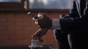 Man Typing a Message Using Mobile Phone at Evening Time in Coffee House. Man with Cup of Cofee Typing a Message Using Mobile Phone at Evening stock video footage