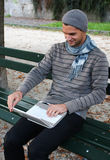Man typing on Netbook. Man writing on Netbook on a Bench Outdoors Royalty Free Stock Images