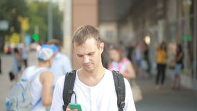 Man typing on phone in the middle of a street. Young guy texting on smartphone. stock footage