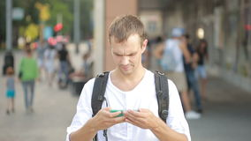 Man typing on phone in the middle of a street. Young guy texting on smartphone. Man typing on telephone in the middle of a street. Young handsome guy texting on stock footage