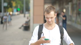 Man typing on phone in the middle of a street. Young guy texting on smartphone. stock video footage
