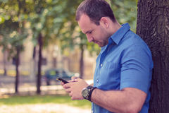 Man typing on the phone in a park. Man seriously typing on the phone in a park Royalty Free Stock Photography