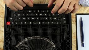 Man is typing on a printed retro typewriter. View from above. Man is typing on a printed retro typewriter, in a large, spacious room. View from above stock footage