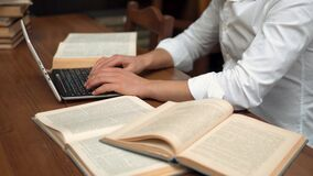 Man Typing while Reading. Closeup of man typing on the keyboard while reading information from book, wearing pristine white shirt, indoor shot at brown wooden stock video footage
