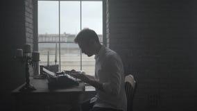 Man typing on retro typewriter side wiew stock video