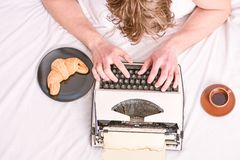 Man typing retro writing machine. Old typewriter on bedclothes. Male hands type story or report using vintage typewriter royalty free stock images