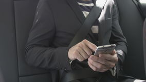 Man typing on a smart phone. Caucasian man typing sms mail on a smartphone in the back seat in a car. For concepts such as sms, text messaging, chat and web stock video