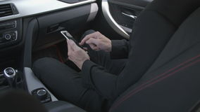 Man typing on a smart phone. Caucasian man typing a sms on a smartphone in the passenger seat in a car. For concepts such as sms, text messaging, chat and web stock video