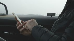 Man typing on a smart phone. Caucasian man typing a sms on a smartphone in the passenger seat in a car. For concepts such as sms, text messaging, chat and web stock footage