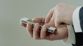 Man is typing on smart phone. Close up of male hands texting a  phone message by one finger stock footage
