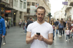 Man typing sms on cell phone and walking on street Royalty Free Stock Photo