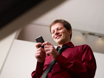 Man typing sms on smartphone and smiling Stock Image
