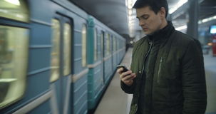 Man typing sms standing on the subway platform. Young man using smart phone to type text message at the underground station, train passing by. Everyday traveling stock video footage