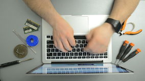 Man typing text on the laptop keyboard in the service center. Top view stock footage