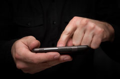 Man typing a text message on a smartphone. Man in black shirt is typing a text message on his smartphone, close up image, focus on hands and the phone device Royalty Free Stock Image