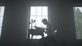 Man typing on a typewriter in a dark room stock video footage