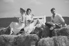 Man or macho typing on vintage typewriter on hay. Friends or students on sunny day on blue sky. Man typing on vintage typewriter on hay. Friends or students on Stock Image