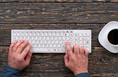 Man typing on a wireless computer keyboard Royalty Free Stock Photos