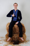 A man in the Ukrainian national costume with a book about busine. The man in the Ukrainian national dress and jeans sitting on a haystack with a book of business Royalty Free Stock Image
