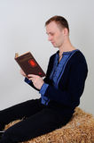 A man in the Ukrainian national costume with a book about busine. The man in the Ukrainian national dress and jeans sitting on a haystack with a book of business Stock Photo