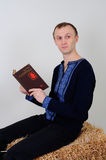Man in the Ukrainian national costume with a book about busine. The man in the Ukrainian national dress and jeans sitting on a haystack with a book of business Royalty Free Stock Image